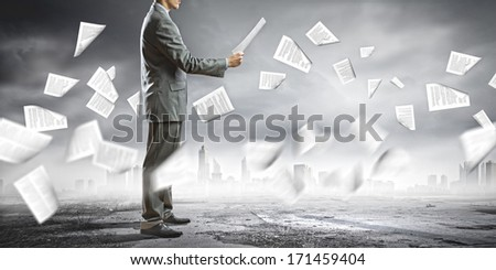 Businessman examining document in hands. Signing contract - stock photo