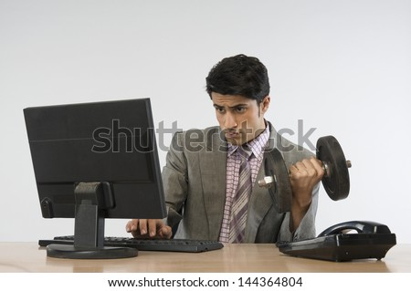 Businessman exercising with dumbbells and working on a computer - stock photo