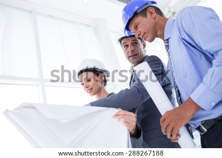 Businessman explaining a blueprint to his colleagues in the office - stock photo
