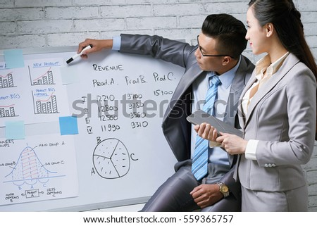 Businessman explaining charts to female coworker