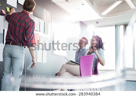Businessman explaining documents to colleagues in creative office - stock photo