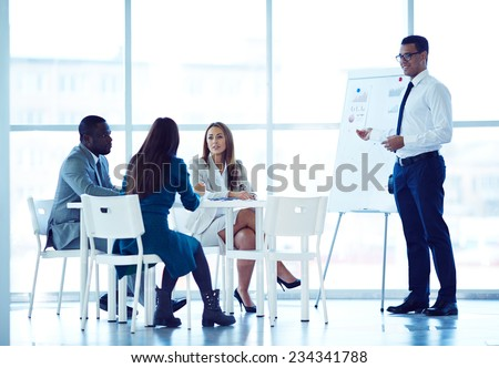 Businessman explaining financial scheme to his partners - stock photo