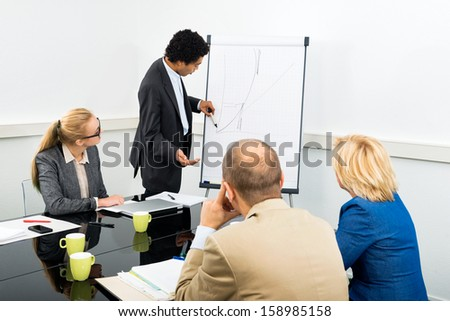 Businessman explaining graph on filpchart to colleagues in conference room - stock photo