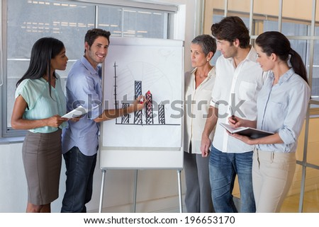 Businessman explaining graph to coworkers in the office - stock photo