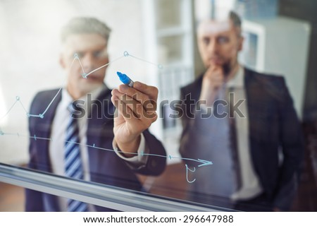 Businessman explaining graph to his colleague - stock photo