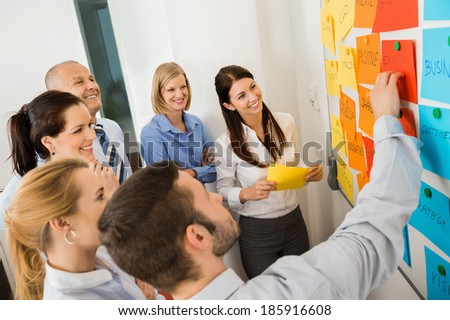 Businessman explaining labels on whiteboard to colleagues in meeting - stock photo