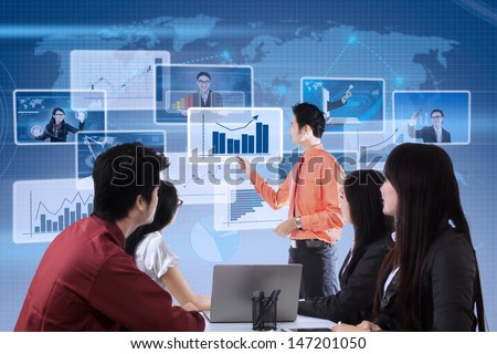 Businessman explaining profit bar chart to the team on blue world map - stock photo