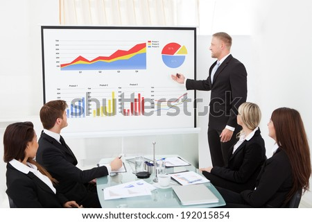 Businessman explaining project to colleagues in conference meeting at office - stock photo