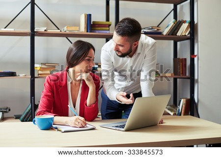 businessman explaining something to woman and looking at her, woman listening and looking at laptop in office