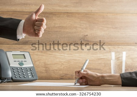 Businessman expressing his approval and satisfaction by making a thumbs up gesture over a contract being signed by his female partner. Conceptual of subscription, employment and business deal. - stock photo