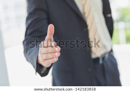Businessman extending hand for handshake in the office - stock photo