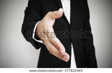 Businessman extending hand, selective focus, shallow depth of field - stock photo