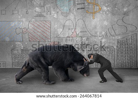 Businessman fighting against black bear with business concept doodles wall background - stock photo