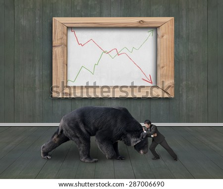 Businessman fighting against black bear with two trend lines of whiteboard, on wooden indoors background. - stock photo