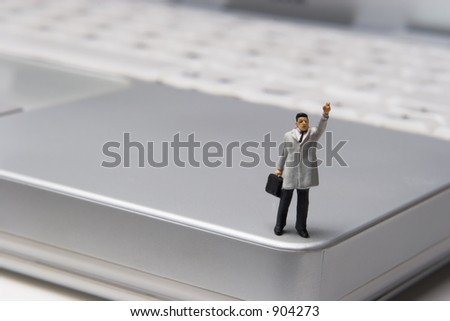 Businessman Figurine on laptop - stock photo