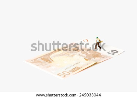 businessman figurine running on a euro banknote,on white background with clipping path - stock photo