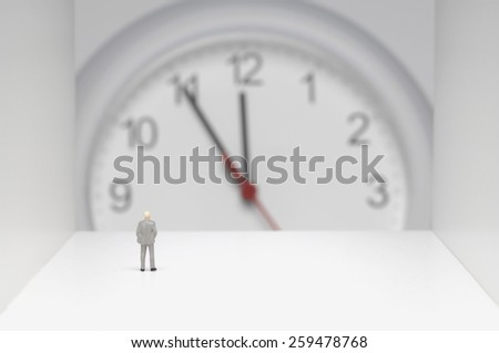Businessman figurine standing in front of clock.