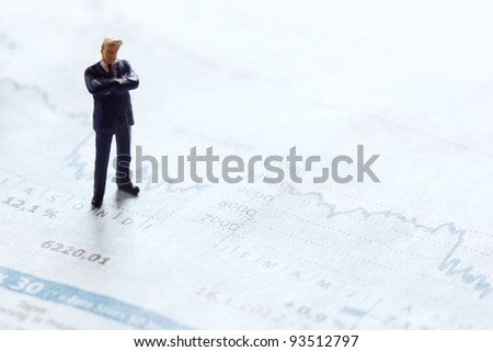 businessman figurine standing upon a financial sector of a newspaper