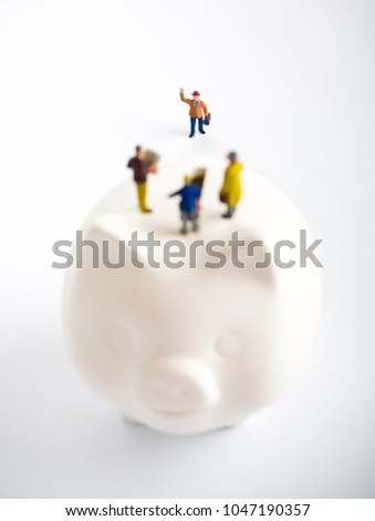 Businessman figurines on a piggybank. Money, business and expectation concept. blur
