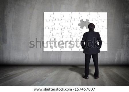 Businessman figuring out puzzle pieces with piece missing on grey wall
