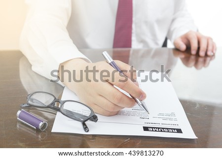Businessman filling a resume on his desk and review before sending to finding a new job with pen and glasses.