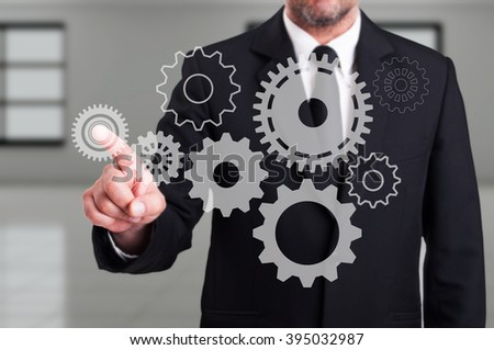 Businessman finger touching a modern digital gear on touchscreen as business or engineering innovation concept
