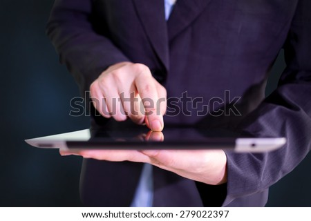 Businessman finger touching screen of a digital tablet