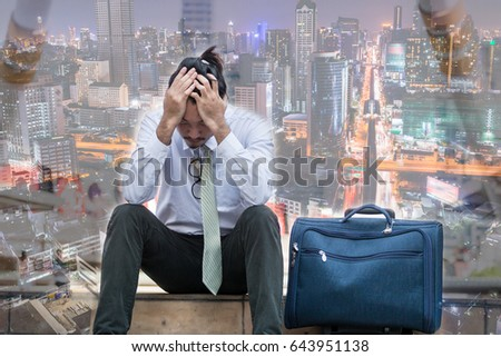 businessman fired from job sitting sad outside office in city background.