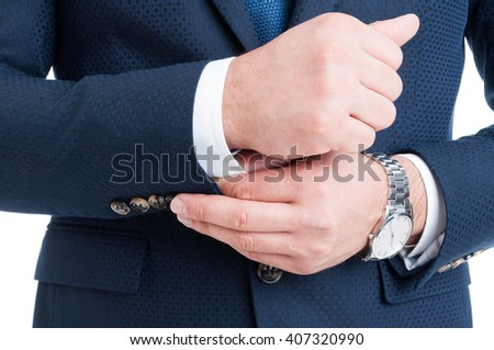 Businessman fixing and adjusting white shirt sleeve under blue suit. Rich and expensive concept - stock photo