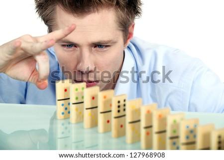 Businessman flicking dominoes - stock photo