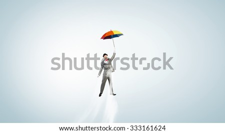 Businessman flying in sky on colorful umbrella