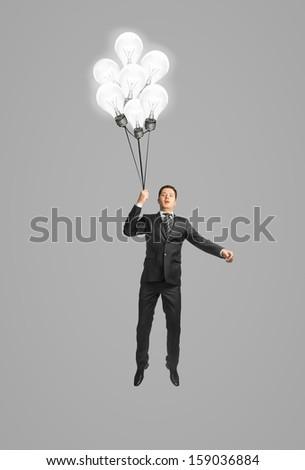 businessman flying on light bulb - stock photo