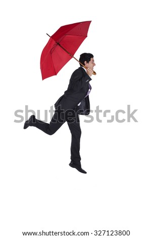 Businessman flying with a red umbrella - stock photo