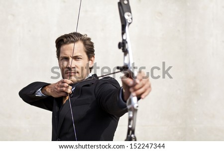 Businessman focusing on his target using a bow and arrow - stock photo