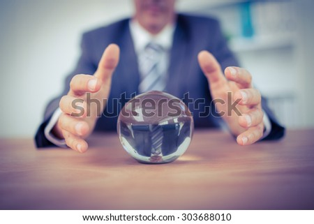 Businessman forecasting a crystal ball in the office - stock photo