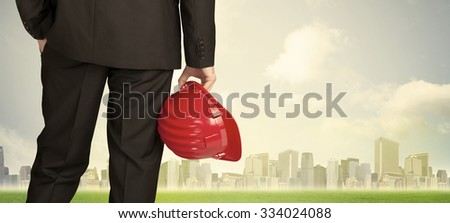 Businessman from the back in front of a city view with clouds and grass - stock photo