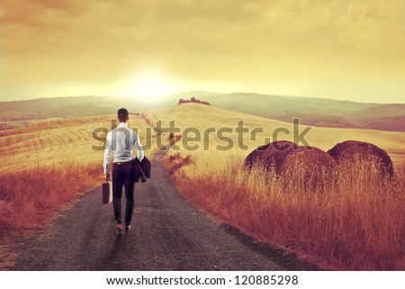 Businessman from the back on a long country road - stock photo