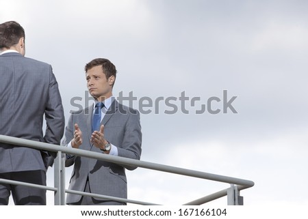 Businessman gesturing while communicating with coworker against sky - stock photo