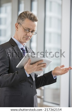 Businessman gesturing while using tablet PC in office - stock photo