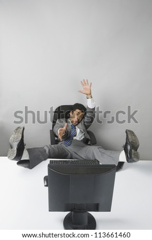 Businessman gesturing with his feet up in front of a desktop PC - stock photo