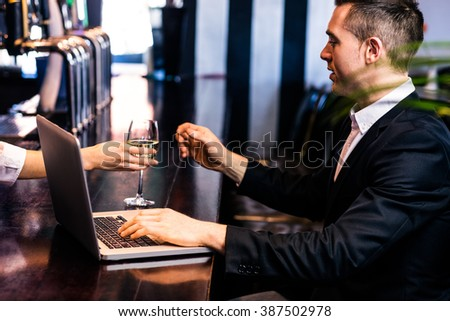 Businessman getting a glass of wine and using laptop in a bar