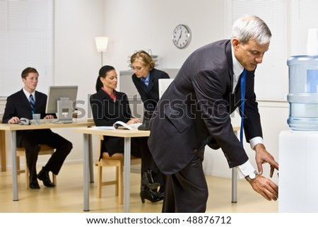 Businessman getting water from water cooler - stock photo