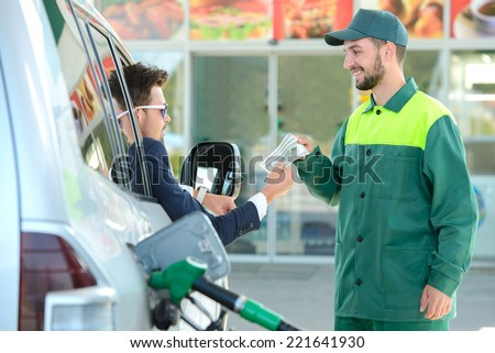 Businessman give money dispensers, filled car on gas station - stock photo