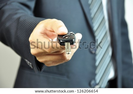 Businessman giving a car key - stock photo