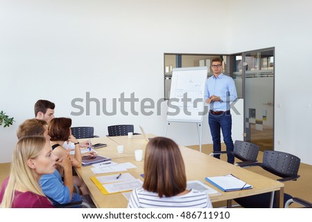 Businessman giving a lecture or presentation to colleagues in the office as they sit around a conference table