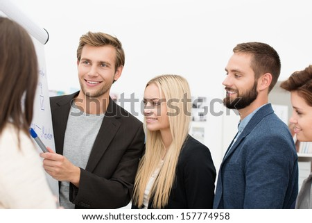 Businessman giving a presentation standing around a flipchart with a group of his colleagues in the office - stock photo