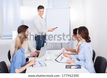 Businessman Giving A Presentation To Colleagues At Workplace - stock photo