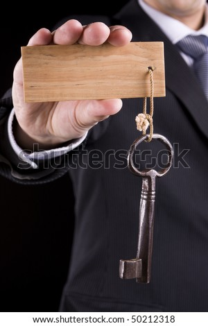 Businessman giving a special key to someone (put your text on the wooden keychain)