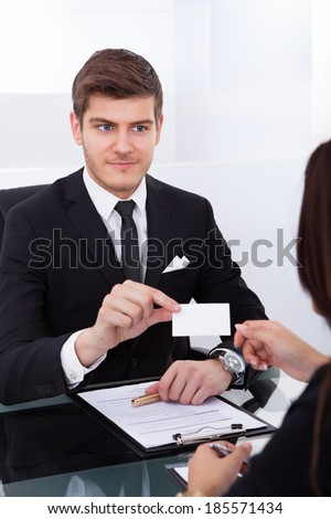 Businessman giving business card to female colleague at desk in office - stock photo