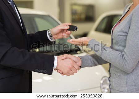 Businessman giving car key while shaking a customer hand at new car showroom - stock photo
